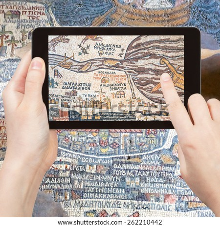 travel concept - tourist takes picture of ancient byzantine map of Holy Land, Madaba on smartphone, Jordan - stock photo