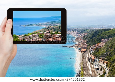 travel concept - tourist takes picture of Ionian Sea coastline and Giardini Naxos town from Taormina city, Sicily, Italy on tablet pc - stock photo