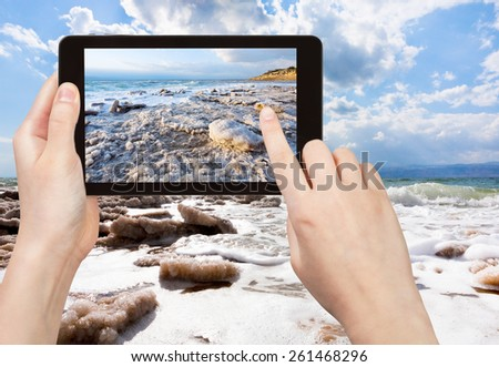 travel concept - tourist taking photo of crystal salt on Dead Sea beach on mobile gadget, Jordan - stock photo