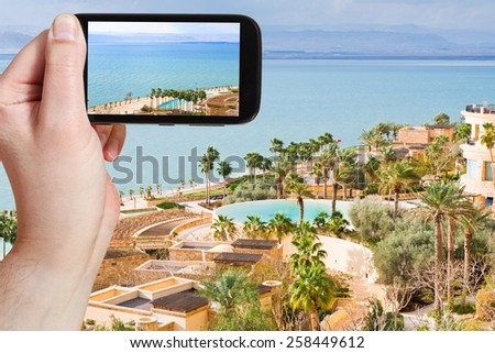 travel concept - tourist taking photo of Dead Sea in Jordan on mobile gadget - stock photo