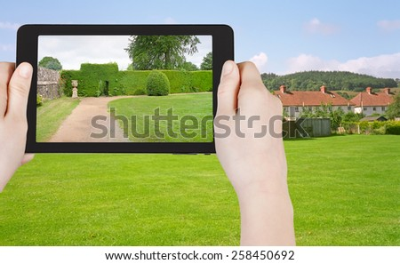 travel concept - tourist taking photo of green lawn in South England country on mobile gadget - stock photo