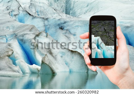travel concept - tourist taking photo of melting snow in briksdal glacier in Norway on mobile gadget - stock photo