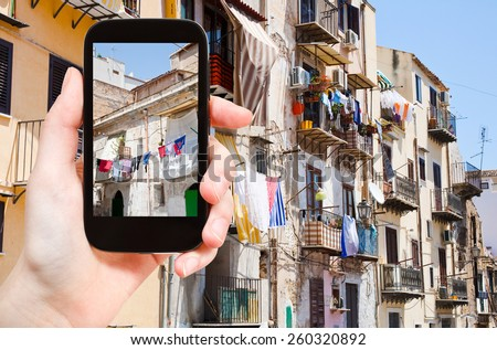 travel concept - tourist taking photo of municipal house in Palermo in summer day, Italy on mobile gadget - stock photo