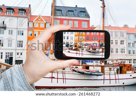travel concept - tourist taking photo of Nyhavn waterfront, canal and entertainment district in Copenhagen on mobile gadget, Denmark - stock photo