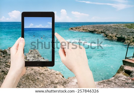 travel concept - tourist taking photo of stone coastline of Caribbean Sea in Bay of Pigs of on mobile gadget, Cuba - stock photo