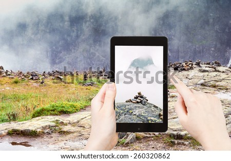 travel concept - tourist taking photo of stone pyramid on mountain plateau in Norway on mobile gadget - stock photo