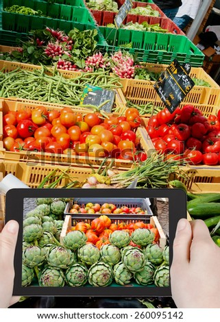 travel concept - tourist taking photo of street vegetable market in France on mobile gadget - stock photo
