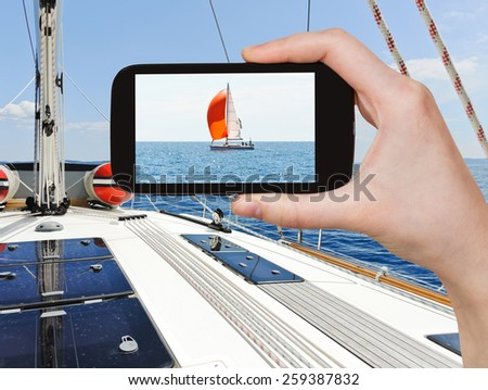 travel concept - tourist taking photo of yacht with red sail in blue Adriatic sea, Dalmatia, Croatia on mobile gadget - stock photo