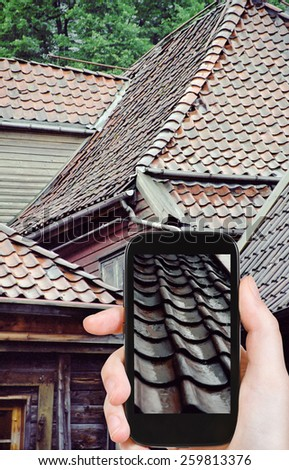 travel concept - tourist taking photo roofs of wooden houses in rain, Bergen, Norway of on mobile gadget