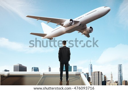 Travel concept with businessman on roof looking at flying by airplane on city background
