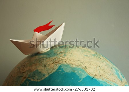 Travel concept with paper boat - stock photo