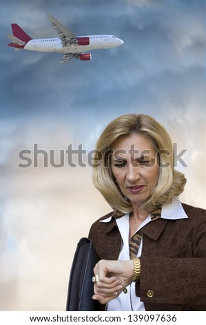 Travel concept with woman looking at wristwatch and airplane flying in the background - stock photo