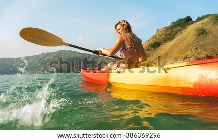 Travel concept. Woman exploring calm tropical bay by kayak.