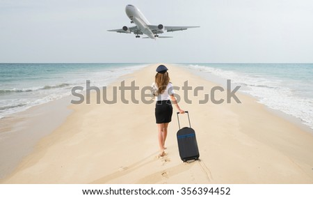 Travel concept. Young woman in flight attendant clothes walking on the beach with suitcase and hat . Overhead fly plane.  - stock photo