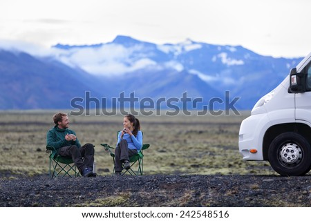 Travel couple by mobile motor home RV campervan. People sitting in chairs relaxing camping and enjoying traveling on Iceland in recreational vehicle. Young couple enjoying coffee in nature landscape. - stock photo