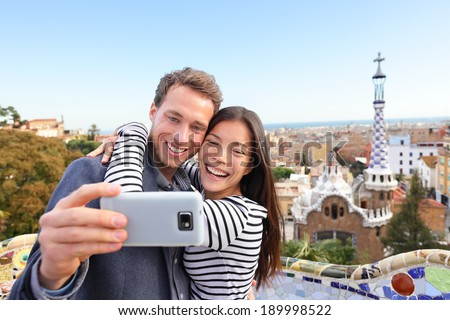 Travel couple happy talking selfie self-portrait with smartphone in Park Guell, Barcelona, Spain. Beautiful young multiracial couple looking at camera taking photo with smart phone smiling in love. - stock photo