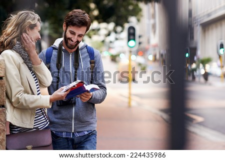 travel couple walking around city on vacation with guide book having fun