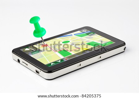 Travel destination, green pin stuck in a GPS device - stock photo
