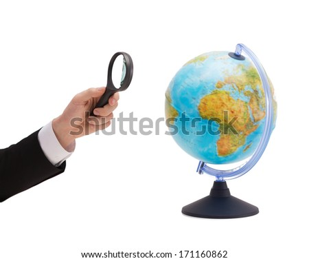 travel, earth, geography and business concept - close up of businessman hand holding magnifying glass over earth globe