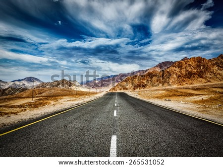 Travel forward concept background - road in Himalayas mountains and dramatic clouds. Ladakh, Jammu and Kashmir, India - stock photo