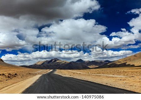 Travel forward concept background - road on plains in Himalayas with mountains and dramatic clouds. Manali-Leh road, Ladakh, Jammu and Kashmir, India - stock photo