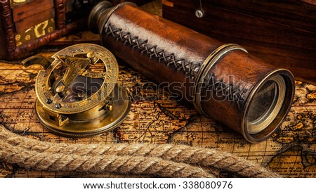 Travel geography navigation concept background - panorama of old vintage retro compass with sundial, spyglass and rope on ancient world map - stock photo