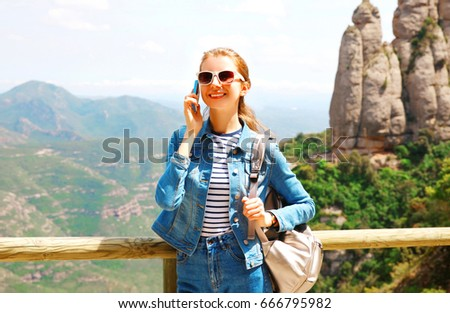 Travel happy smiling woman talking on a smartphone over mountain Spain background