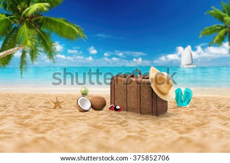 Travel holiday vacation suitcase with sunglasses, starfish, straw hat and beach slippers on the beautiful beach with palm trees. Advertisement on travel suitcase - stock photo