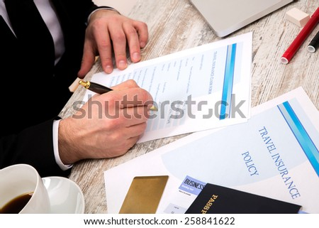 Travel insurance application form with a boarding pass and a passport  - stock photo