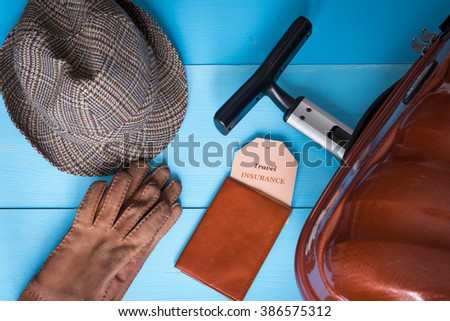 Travel insurance concept. Suitcase, hat, gloves, passport case, insurance tag. Insurance tag text is easily replaceable. - stock photo