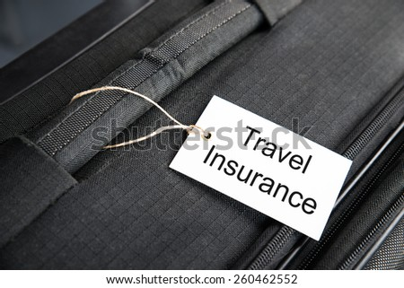 Travel Insurance Label Tied To A Suitcase - stock photo