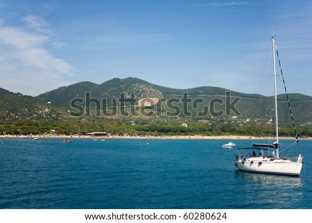 Travel - Italy. Boat floating on the blue waters of the Countess Cove (Cala Della Contessa), Elba Island.