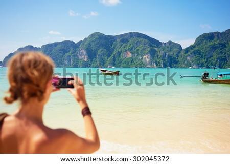 Travel lifestyle. Female tourist taking photo of beautiful lagoon on smartphone. - stock photo