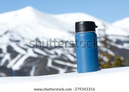 Travel Mug In The Mountains - This is an image of a blue travel coffee mug sitting in a snow bank with a big mountain in the background. Shot with a shallow depth of field.  - stock photo