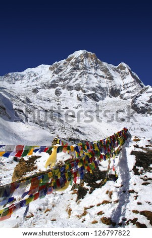 Travel Nepal: Annapurna South peak in Himalaya with buddhist prayer flags in the foreground
