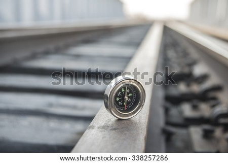 Travel or transportation Concept. metal modern Compass lie on wooden and metal railway in perspective background Empty space for inscription. No train on road. Direction idea, symbol, sign - stock photo