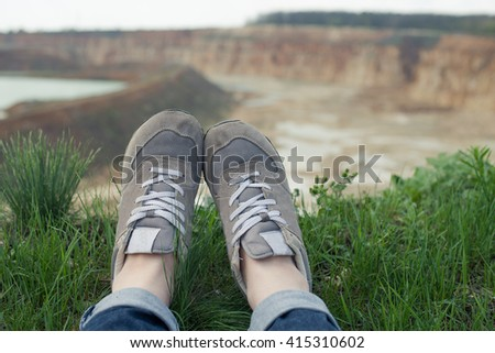 Travel photo: hipster tourist sneakers feet relaxing in mountains, lake in tha beckground, freedom concept