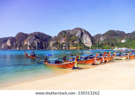 Travel photo of amazing Koh Phi Phi in Thailand. Deep plus clear water, mountains and local boats in hot tropical exotic island. - stock photo