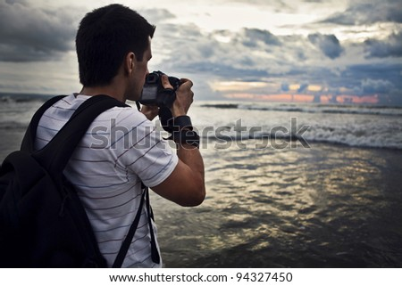 Travel photographer with digital camera making photo of the nature. - stock photo