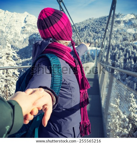 "Travel picture from the Austrian Alps in winter. Woman invites her boyfriend to follow her to the longest suspension bridge ""Highline 179"" in the Tyrolean Alps. Winter travel and hike destination. - stock photo"
