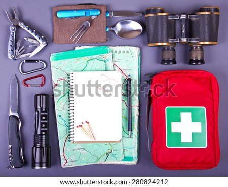 Travel set. Tourist outfit for camping or hiking. Various professional tools and items for outdoors pastime on gray background. Place for your text. - stock photo