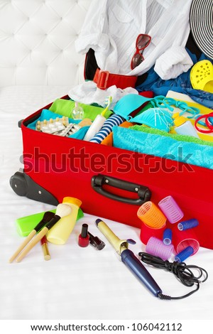 Travel suitcase packed for woman vacation with personal belongings. Concept. Preparation for holidays in sea resort: what to pack to the luggage. - stock photo