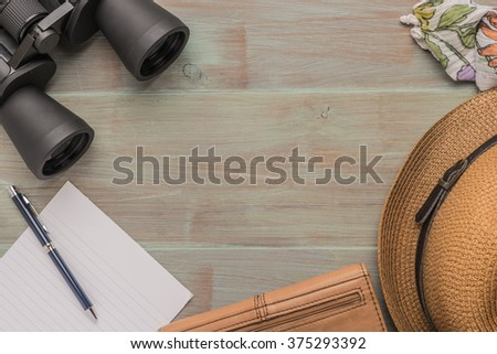 Travel, summer vacation, tourism and objects concept - close up of binoculars, hat, pen, paper and scarf on wooden table. Top view with copy space. - stock photo