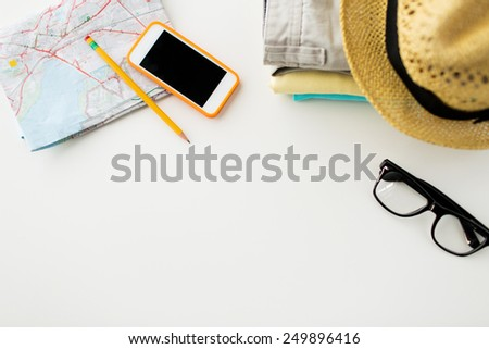 travel, summer vacation, tourism and objects concept - close up of folded clothes, smartphone and touristic map on table - stock photo
