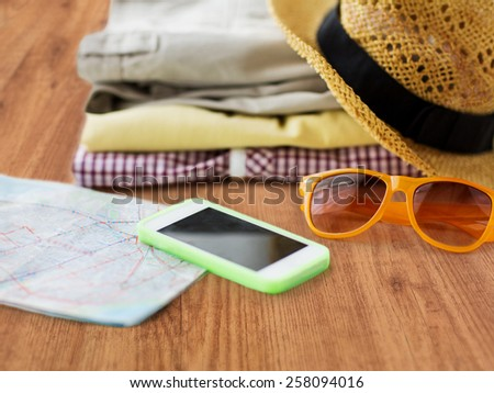 travel, summer vacation, tourism and objects concept - close up of folded clothes, smartphone and touristic map on wooden floor - stock photo