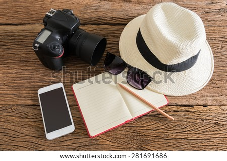 travel, summer vacation, tourism and objects concept. close up of hat, notebook, pencil, camera, smartphone and sunglasses on wooden table. Photo retro style - stock photo
