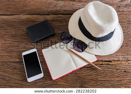 travel, summer vacation, tourism and objects concept. close up of hat, notebook, pencil, wallet, smartphone and sunglasses on wooden table. Photo retro style - stock photo