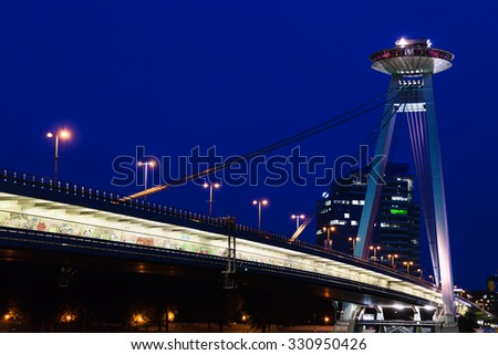 travel to Bratislava city - view of Most SNP (Bridge of the Slovak National Uprising, UFO Bridge, Novy most, New Bridge) road bridge over Danube river in Bratislava in night - stock photo