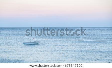 travel to Sicily, Italy - one boat on blue water of Ionian sea near Giardini Naxos town in blue summer evening