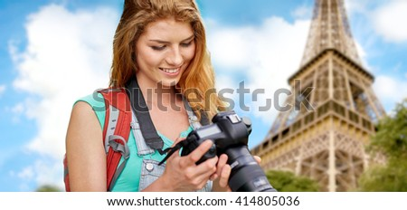 travel, tourism and people concept - happy young woman with backpack and camera photographing over eiffel tower background - stock photo